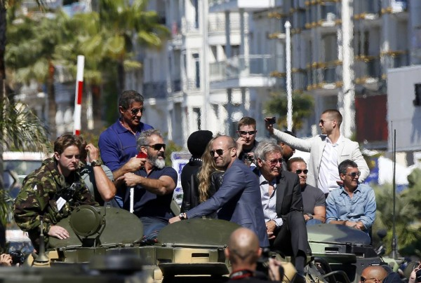 """Cast members Sylvester Stallone, Mel Gibson, Jason Statham, Harrison Ford, Arnold Schwarzenegger and Antonio Banderas  pose on a tank as they arrive on the Croisette to promote the film """"The Expendables 3"""" during the 67th Cannes Film Festival in Cannes"""