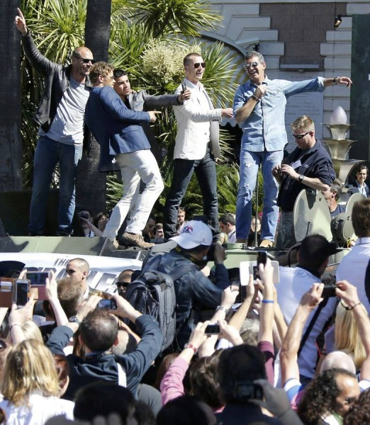 """Cast members Randy Couture, Kellan Lutz, Victor Ortiz, Glen Powell and Antonio Banderas pose  on a tank as they arrive on the Croisette to promote the film """"The Expendables 3"""" during the 67th Cannes Film Festival in Cannes"""