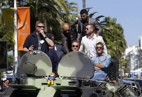 """Cast members Victor Ortiz, Arnold Schwarzenegger, Victor Ortiz, Glen Powell and Antonio Banderas pose on a tank as they arrive on the Croisette to promote the film """"The Expendables 3"""" during the 67th Cannes Film Festival in Cannes"""